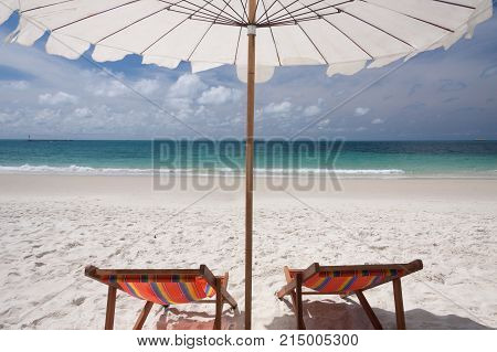 Umbrella and twin chairs on a beautiful tropical beach.