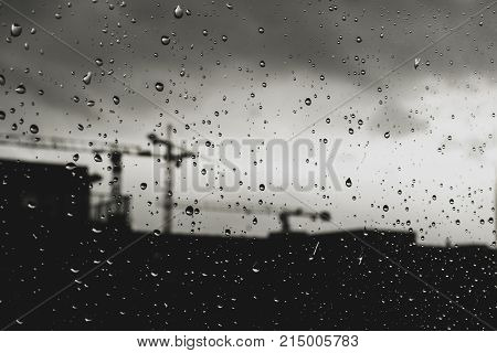 Raindrops On Window With Unfocused Urban Background With Cranes