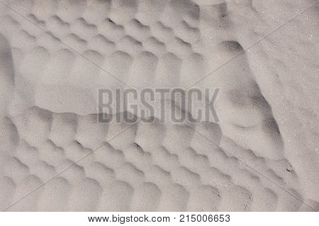 Texture of wheel track on white sand.