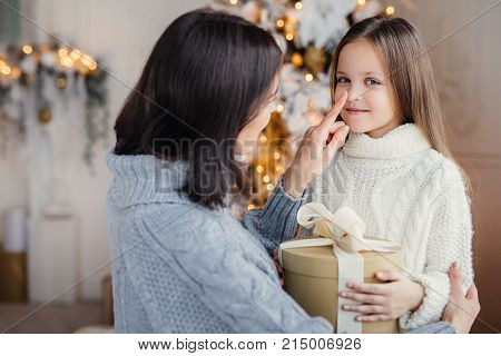 Portrait of adorable little kid and mother, touches her little nose, gives wrapped gift box, prepares little surpise for daughter, gives present near decorated New Year tree. Christmas and New Year
