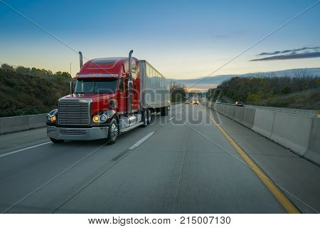 Red semi-truck tractor trailer 18 wheeler on highway at sunrise
