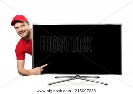 smiling young man in red uniform pointing on blank tv screen