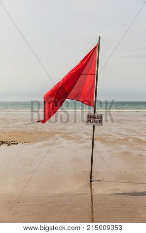Red flag on the beach with a no swimming sign in French