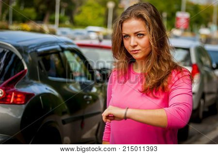 Beautiful Caucasian young woman unhappy with someone to arrive late for the meet. Wait for a long time stock image. Precious time.