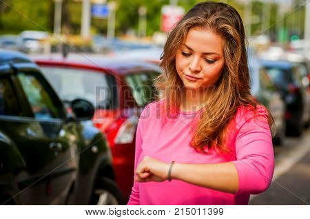Unhappy and upset young Caucasian woman looking at her watch tired of waiting. Her boyfriend is late for the date.