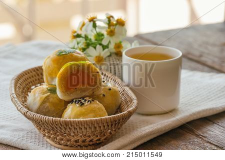 Delicious Chinese pastry or moon cake filled with mung bean paste and salted egg yolk on wood basket served with tea on wood table in side view close up with copy space. Homemade Chinese pastry. Moon cake or Chinese pastry ready to served.