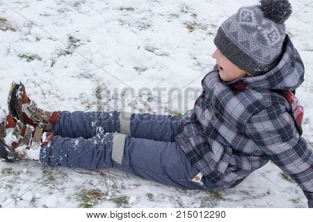 One boy was sitting on white snow and riding