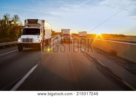 18 wheeler semi trucks on highway with sun flare