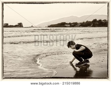 Boy playing with the sand and waves in Laganas beach Zakynthos islandGreece. Soft sepia toned in an old style frame.