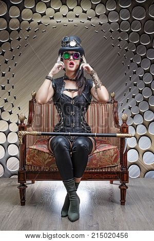 Beautiful girl in a felt hat, corset and glasses steampunk sitting in a chair