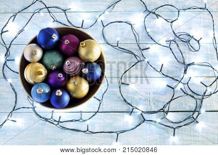 Fairy Lights and Christmas Baubles on Wooden Background
