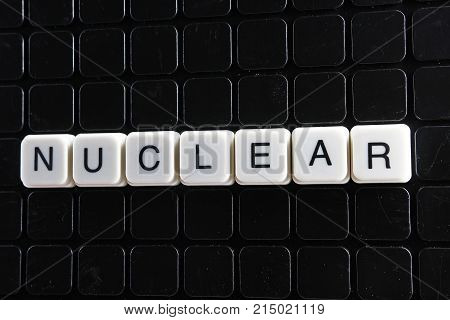 Nuclear white text word on black cover. Text word crossword. Alphabet letter blocks game texture background nuclear.