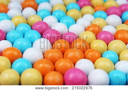 Shiny sugar coated round chocolate balls as background. Candy bonbons multicolored texture. Round candies sweets pattern concept. Food photo studio photography. Candy background. Texture background.