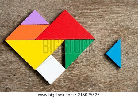 Colorful tangram puzzle in heart shape wait to fulfill on wood background (Concept of happy family love fulfillment)