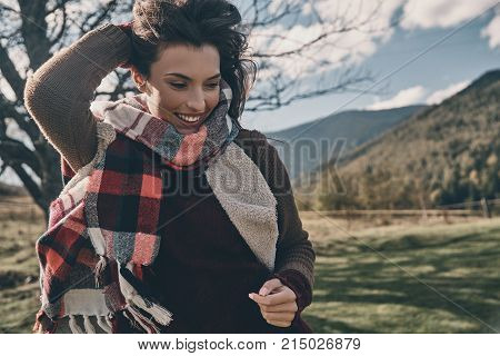 Full of life energy. Attractive young woman smiling and keeping hand in hair while running on the valley in mountains outdoors