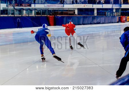 back two men speed skaters race and coach on ice rink