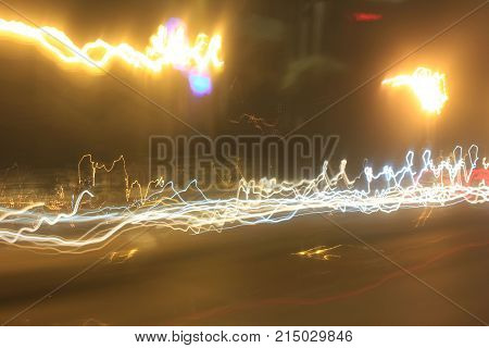 Abstract Lights Background with Vibrant Soft Yellow, Golden and White Light Lines and Trail Patterns. Long Exposure Design Image of City Street at Night. Electrical Discharge Flash Glow Illusion