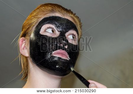 Girl In A Cosmetic Black Mask. Cleansing Mask Of Aspirin And Activated Carbon. Black Cosmetic Face M