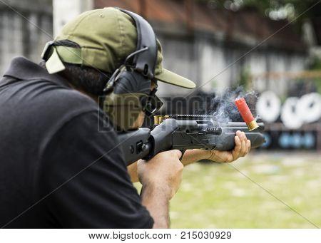Man shooting on an outdoor shooting range selective focus