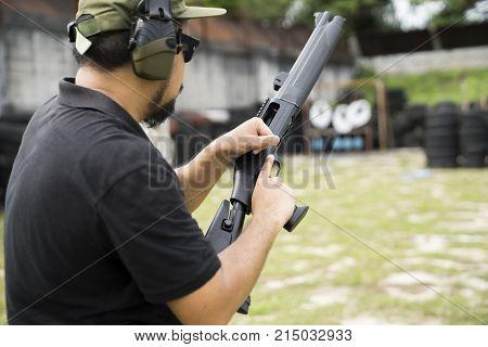 Man changing bullets in the shotgun, Man loading bullets into gun,
