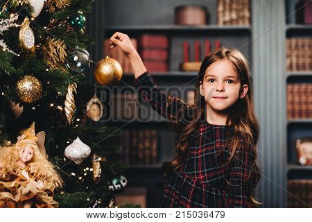 Small little kid decorates Christmas tree indoors, looks directly into camera, holds glass ball, being glad to have winter holidays. Little adorable girl wears dress decorates New Year tree alone