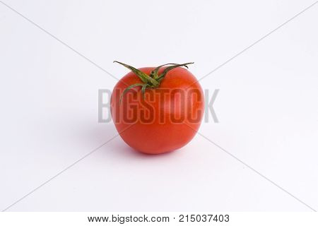 Fresh tomatoes isolated on white background. One whole tomato on the white background. Tomatoes. One fresh delicious whole tomato isolated on a white background.