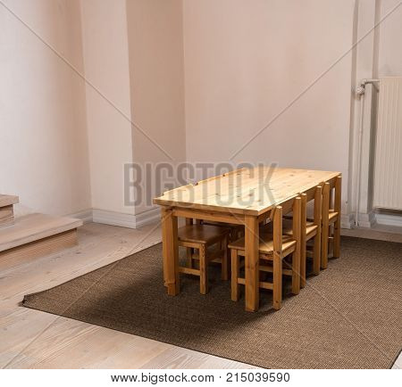 Eye level view of a wooden table and six chairs sized for children in classroom or play group