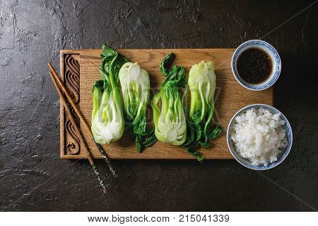 Stir fried bok choy or chinese cabbage with soy sauce and bowl of rice served on decorative wooden cutting board with chopsticks over dark texture background. Top view with space. Asian style dinner
