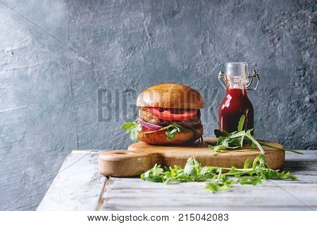 Homemade burger in classic bun with tomato sauce, arugula, meat, cheese, onion, bottle of ketchup on wood serving board over white wooden plank table. Rustic style. Homemade fast food.