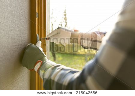 Handyman fixing the window with screwdriver on a sunny day