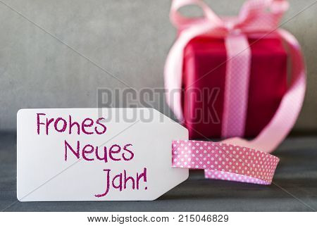 Label With German Text Frohes Neues Jahr Means Happy New Year. Pink Gift Or Present With Gray Cement Background
