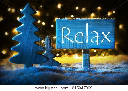 Sign With English Text Relax. Blue Christmas Tree With Snow And Magic Glowing Lights In Backround. Card For Seasons Greetings.