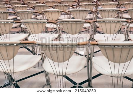 A row of metallic, chromated beige chairs in the open air.