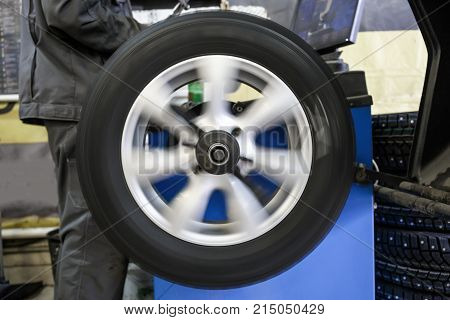Process of balancing and fitting car tire wheel in motion, auto repair service, garage mechanic