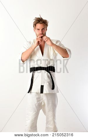 Guy Poses In White Kimono With Black Belt. Japanese Karate