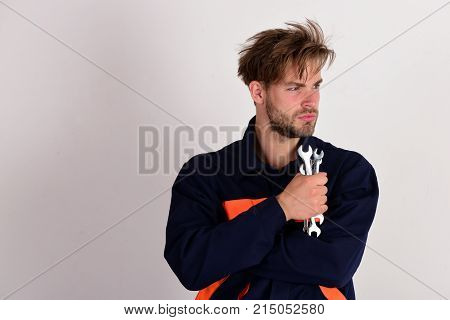 Man With Serious Face In Uniform Holds Wrench Tools