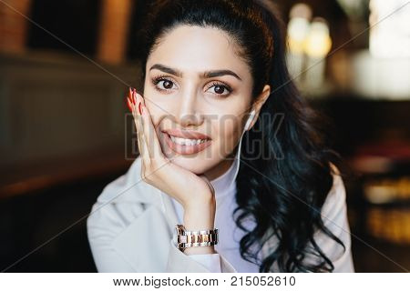 Close up portrait of beautiful brunette female with dark warm eyes, curling eyelashes, thin well-shaped eyebrows and full lips holding hand on cheek wearing elegant watch having earphones in ears