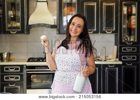 Plump Woman Cooking On The Kitchen. Mature Woman In Pastel Apron Holding Bottle Of Milk And One Egg