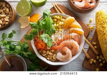 A delicious shrimp noodle bowl with rice noodle mandarin orange grilled corn peanuts shredded carrot cilantro and toasted sesame dressing.