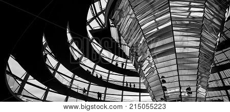 BERLIN GERMANY - OCTOBER 21 2017: People walking inside the Reichstag Dome. It is a glass dome constructed on the top of the Reichstag (Bundestag) building designed by architect Norman Foster