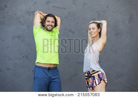 Attractive Woman Exercising With A Personal Trainer Outside At Sunny Day In Urban Enviroment