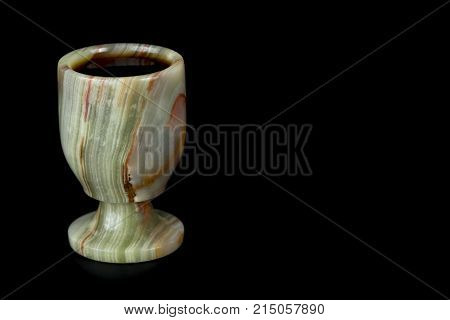 Stone glass from onyx on a black background. A capacity for a drink made of stone.