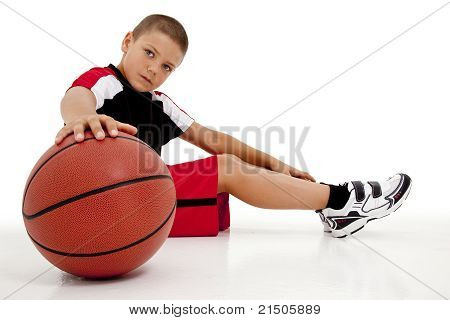 Portrait over white of young boy child basketball player sitting with ball relaxing. poster