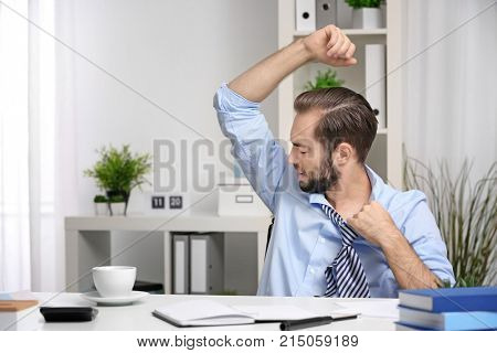 Young man sweating in office