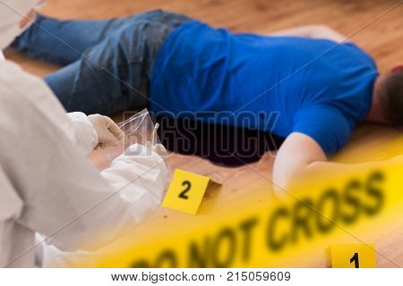 investigation, forensic examination and people concept - criminalist collecting evidence of murder of man at crime scene fenced by police tape