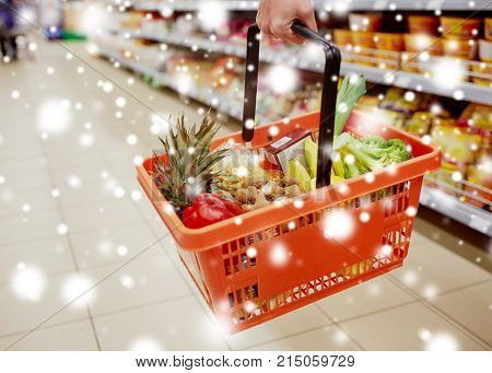 sale, shopping, consumerism and people concept - woman with food basket at grocery store or supermarket over snow