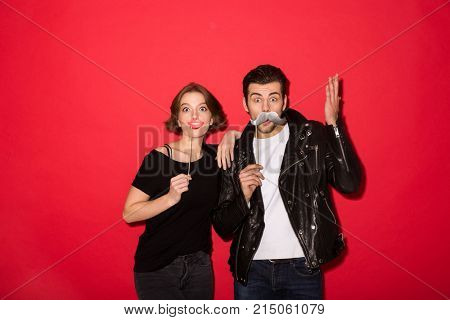 Funny punk couple posing with fake mustache and lips while looking at the camera over red background