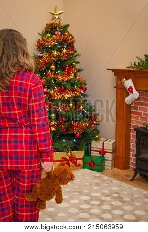 A young girl holding a teddy bear on Christmas morning as she discovers that Santa has been and left lots of gift wrapped presents under the tree.