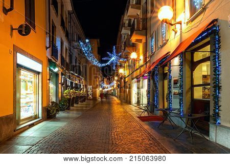 ALBA, ITALY - DECEMBER 07, 2011: Pedestrian street and shops in Old Town of Alba illuminated and decorated for Christmas holidays. This area is very popular with locals and tourists visiting the town.