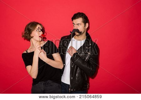Playful punk couple posing with fake mustache, lips and eyeglasses while looking to each other over red background